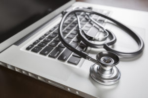 Medical Stethoscope Resting on Laptop Computer Keyboard.