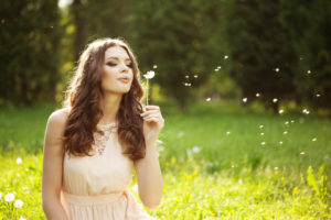 Beautiful woman blowing a dandelion